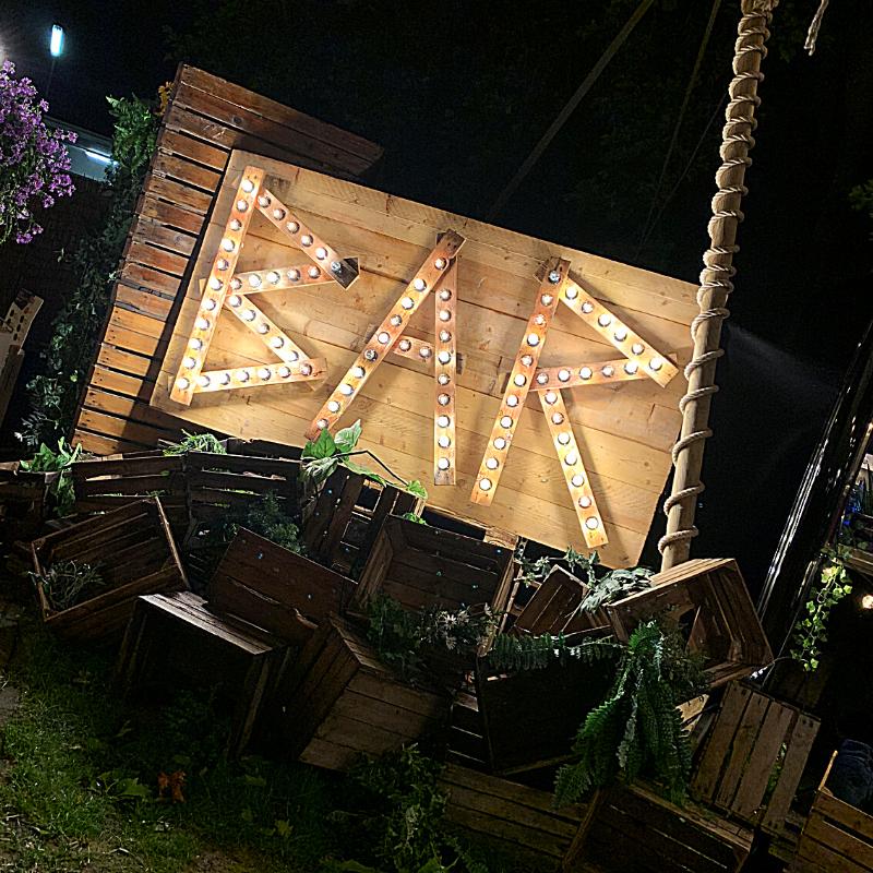 De Dessert Club - Een houten bord met in lampjes geschreven Bar