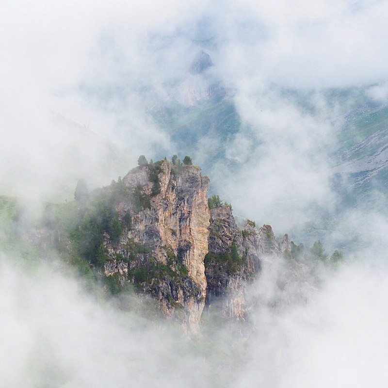 Door de wolken heen zie je een bergkam - Ischgl Oostenrijk